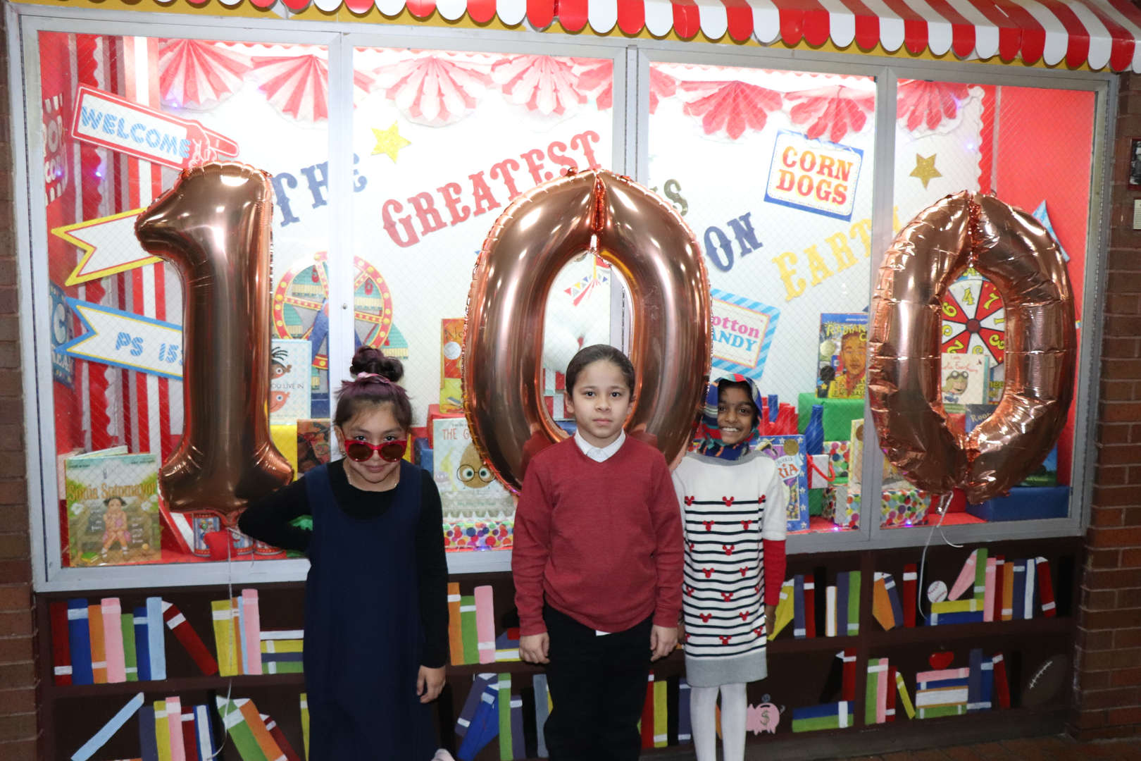 Some more students dressed like they are 100 in front of the number 100 balloons.