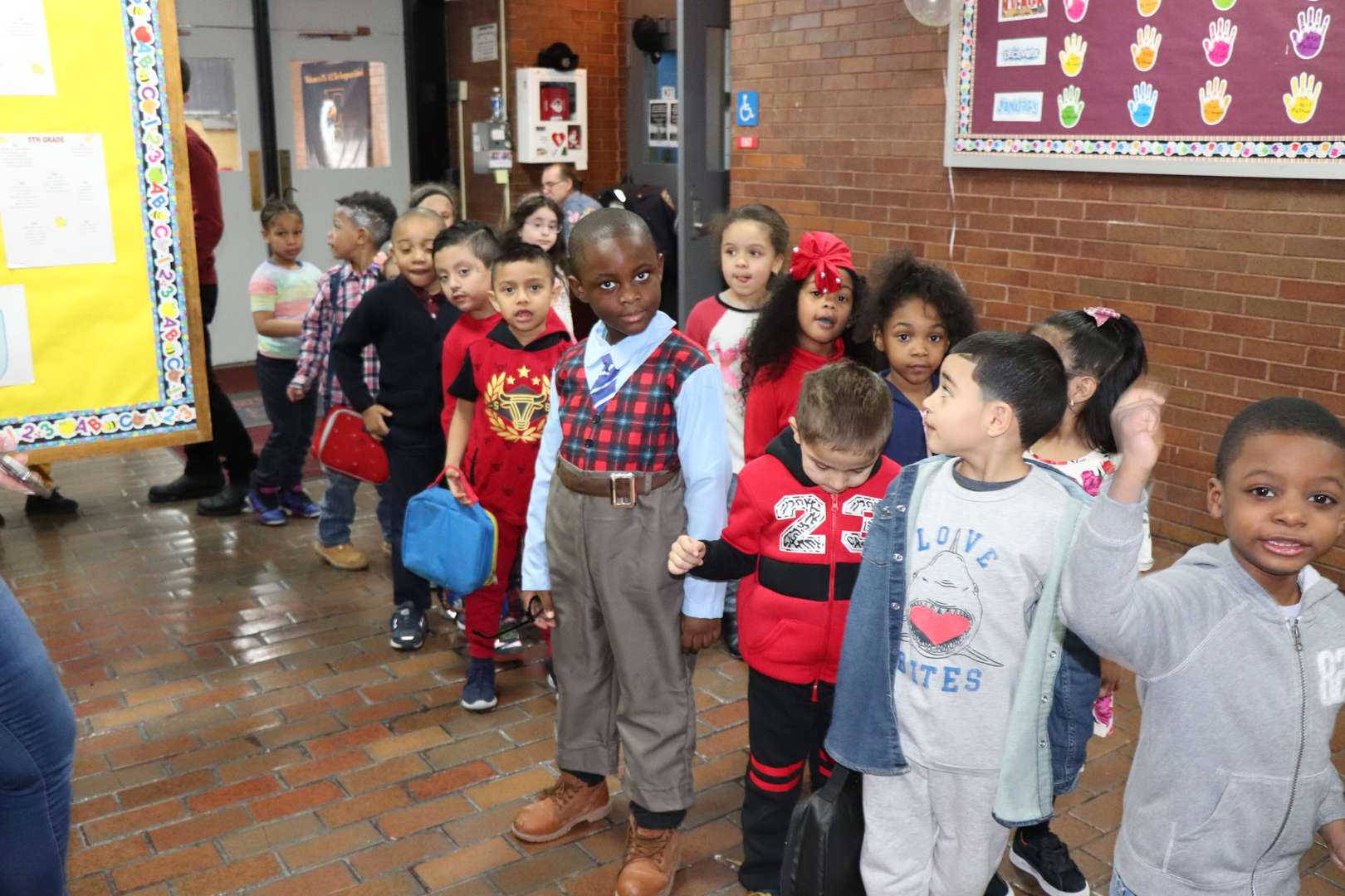 Students waiting to go to lunch while celebrating 100 day and Valentine's Day.