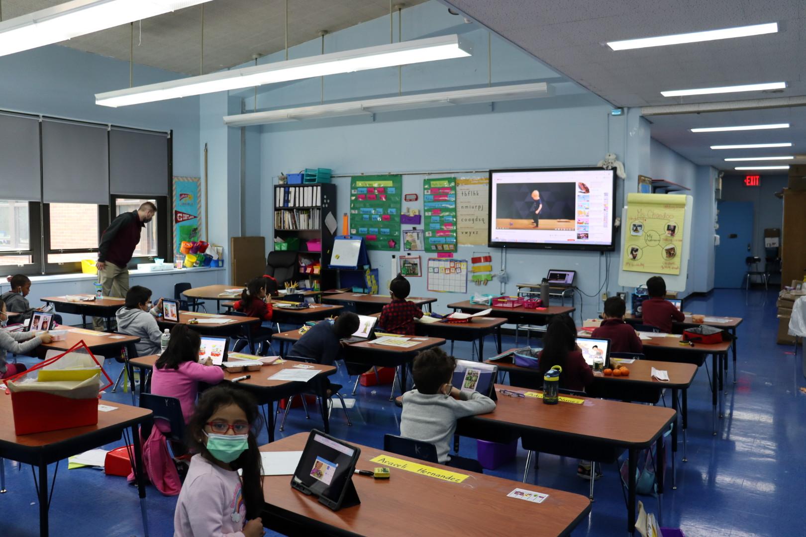 Ms. Chandoo's kindergarten class reading with Mr. LaGreca.