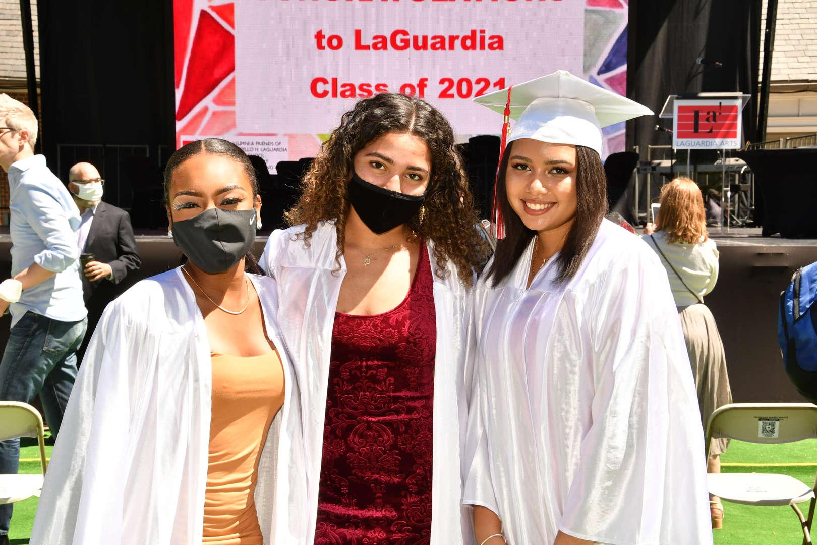 Three graduates posing after ceremony