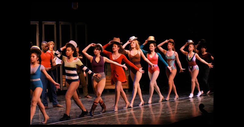"""Female cast rehearsing """"One"""" with  hats."""
