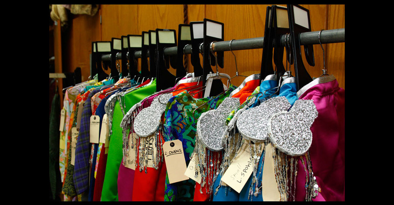 Costume rack with brightly colored marching band costumes.