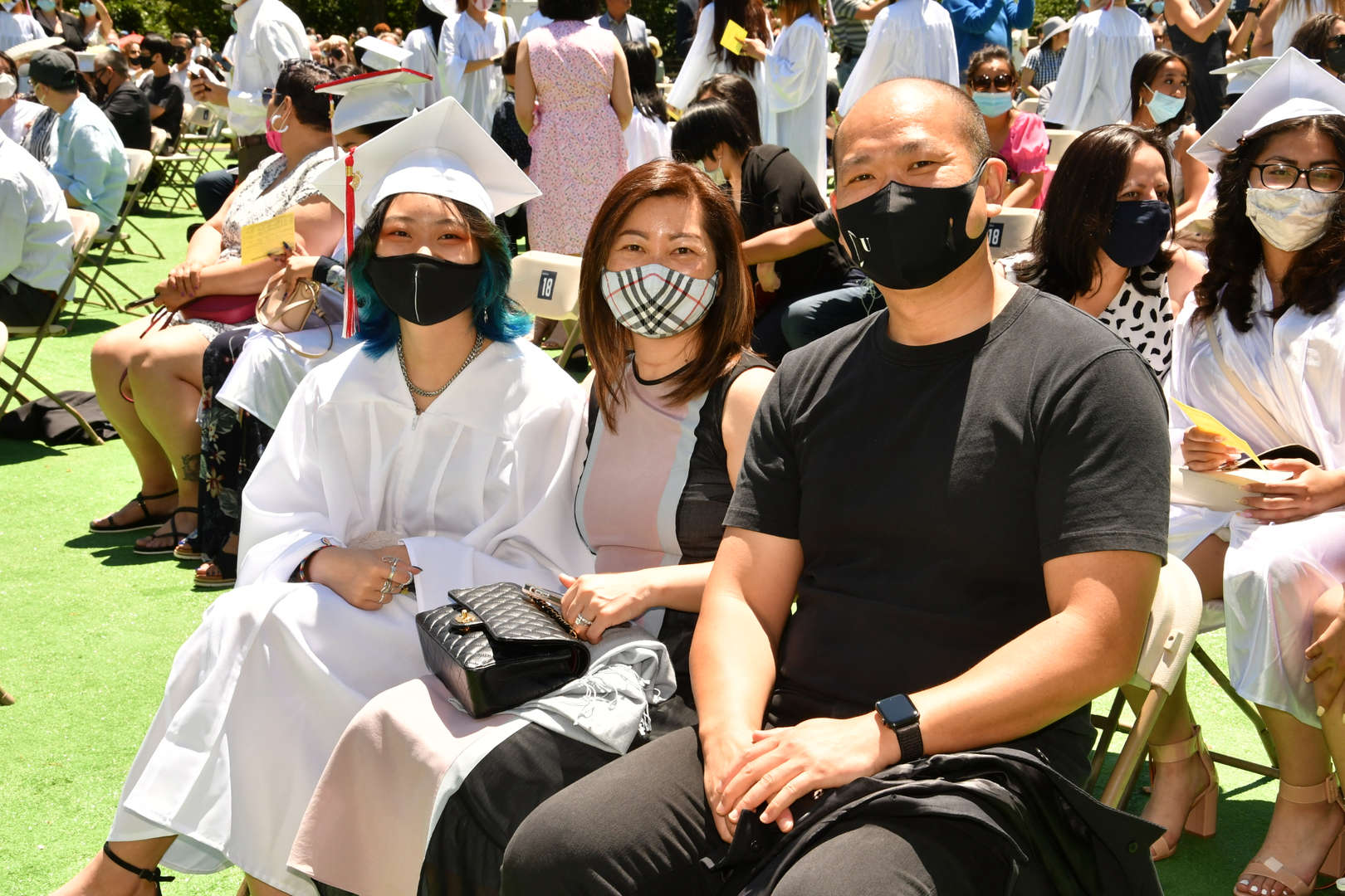 graduate seated with family members