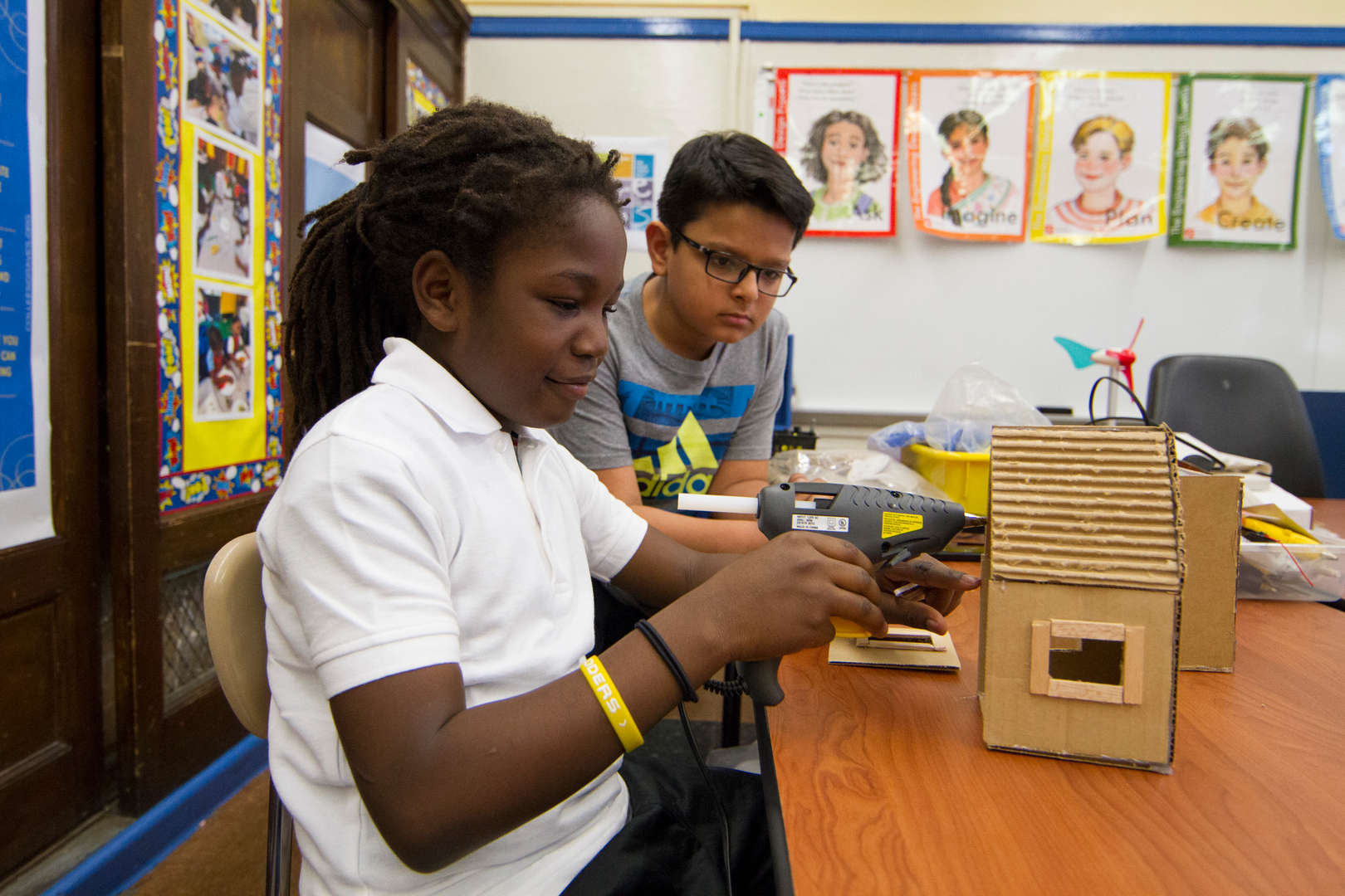 Students using hot glue to construct model house