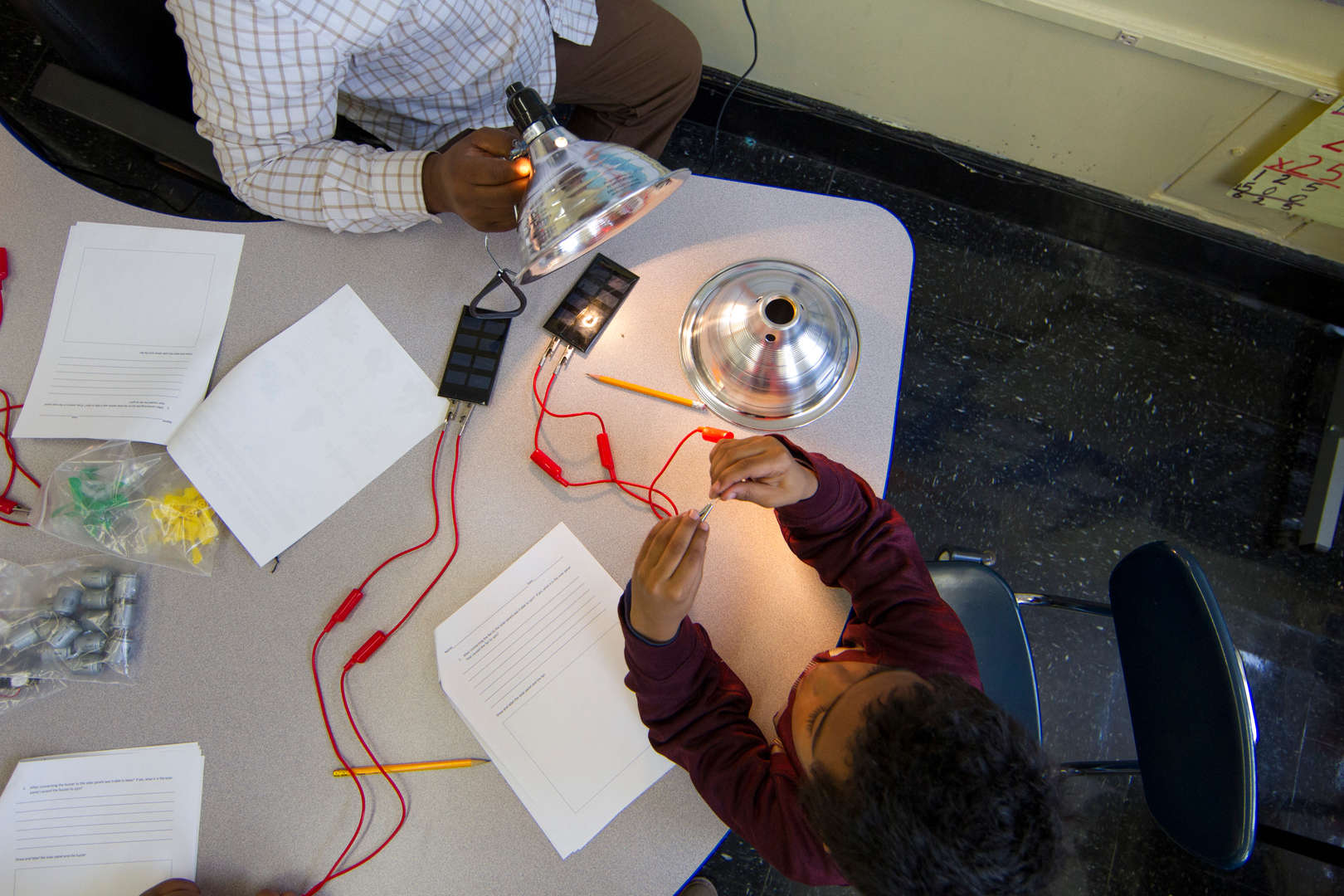 Student creating circuit to light bulb