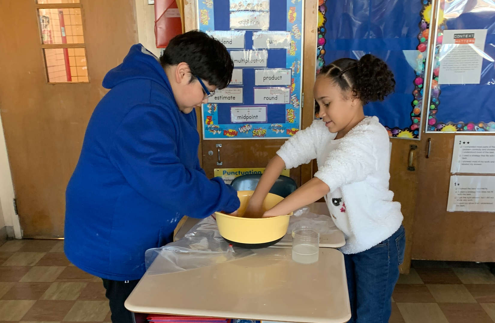 Students mixing ingredients in a bowl.