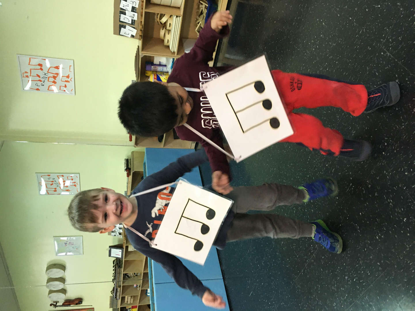 Two boys with signs that represent musical notes