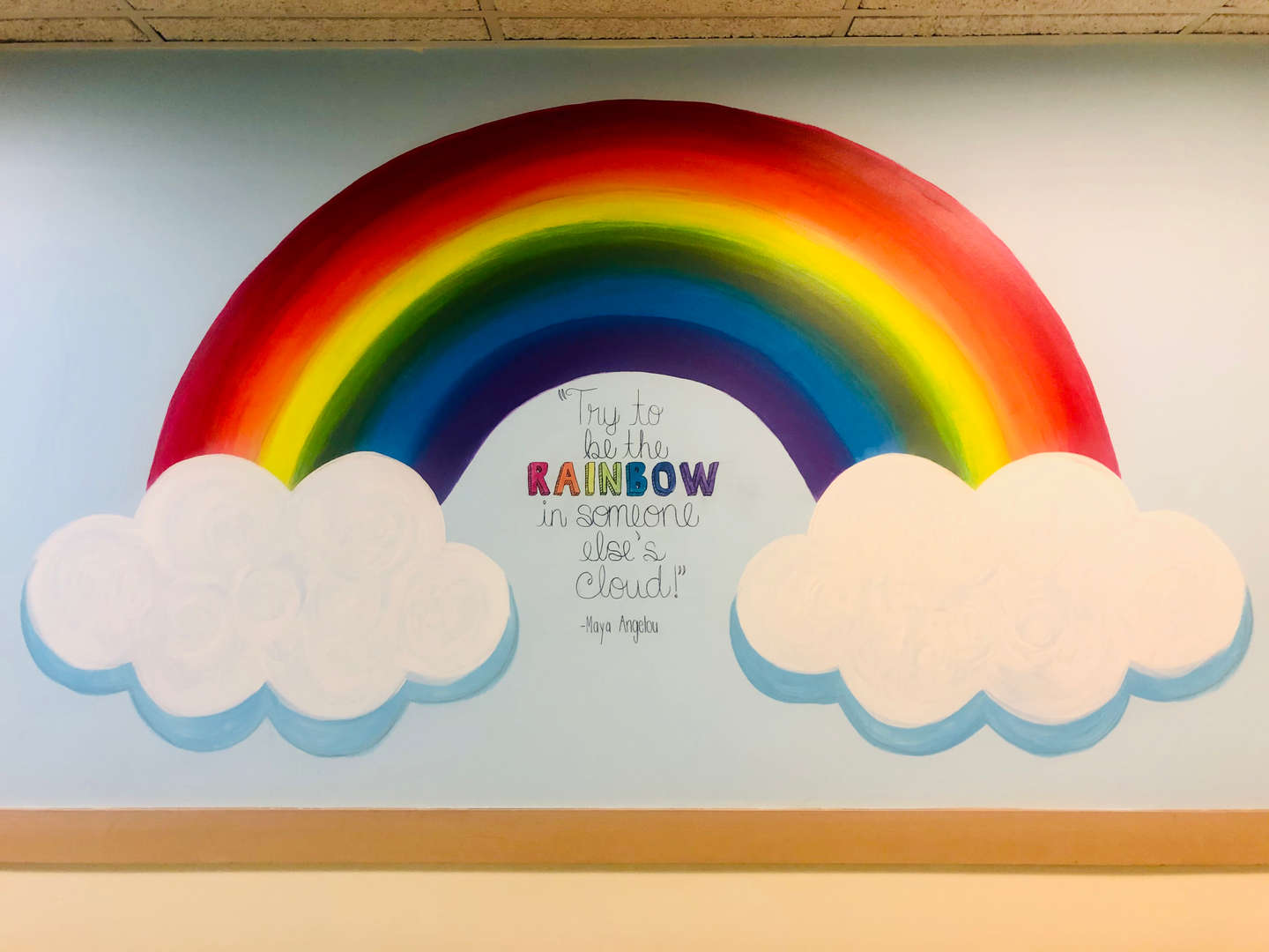"rainbow mural with Maya Angelou quote, ""Try be be a rainbow in someone else's cloud."""