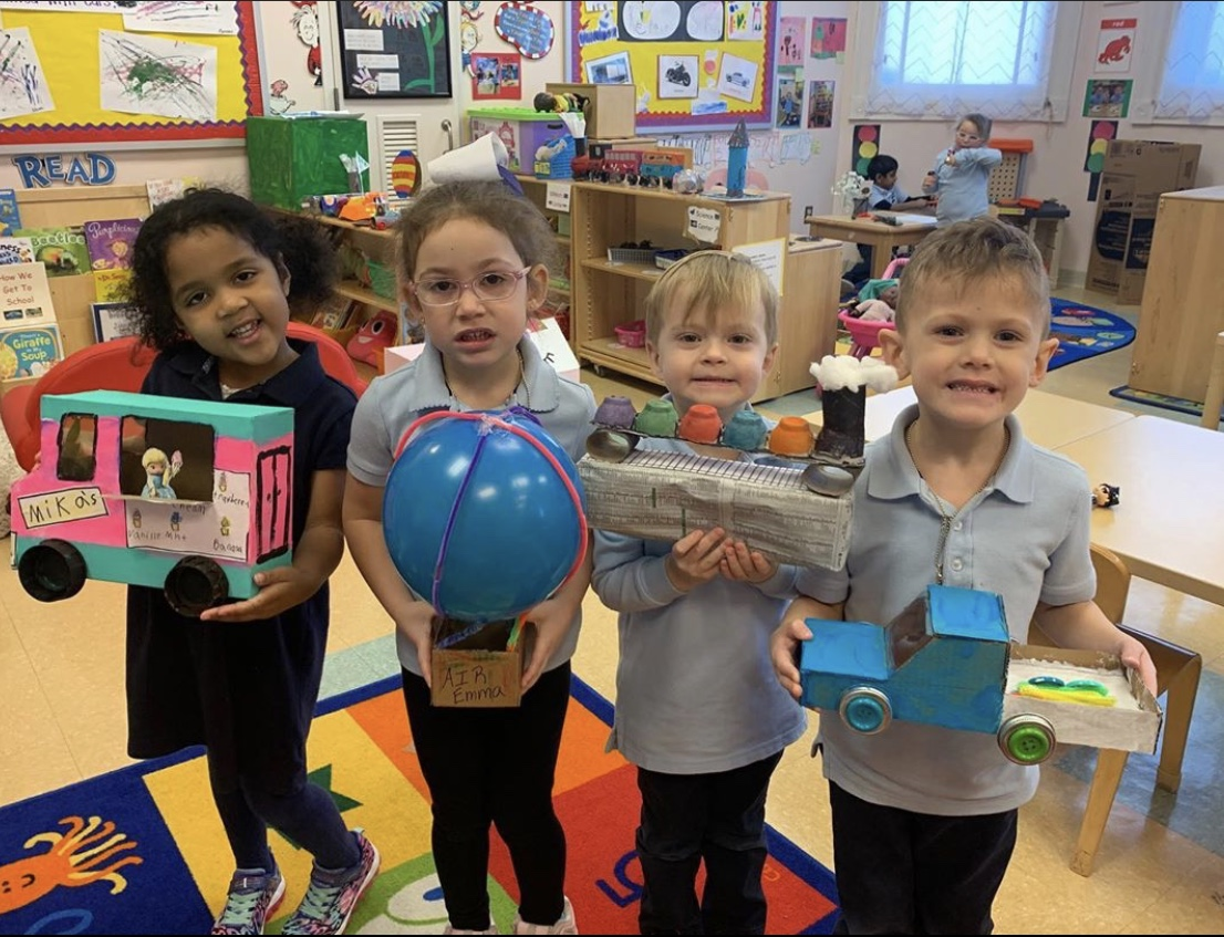Pre K students showing different forms of transportation created from recycled items