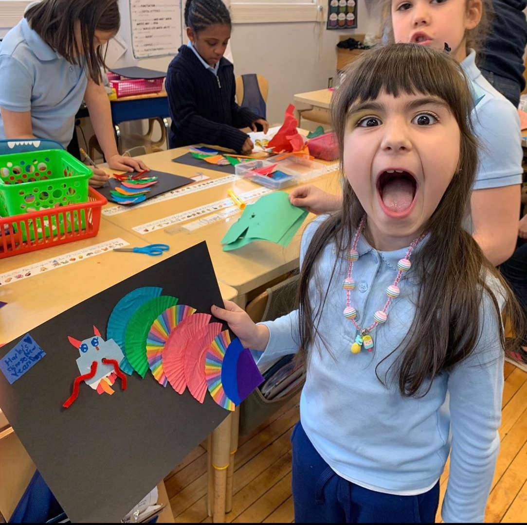 3rd grade student showing her dragon artwork making a dragon face