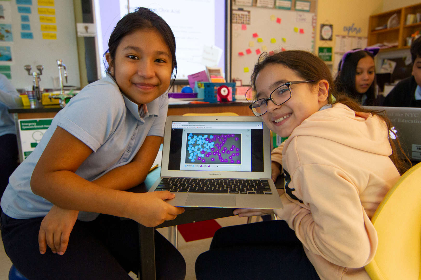 5th Graders showing project on laptop