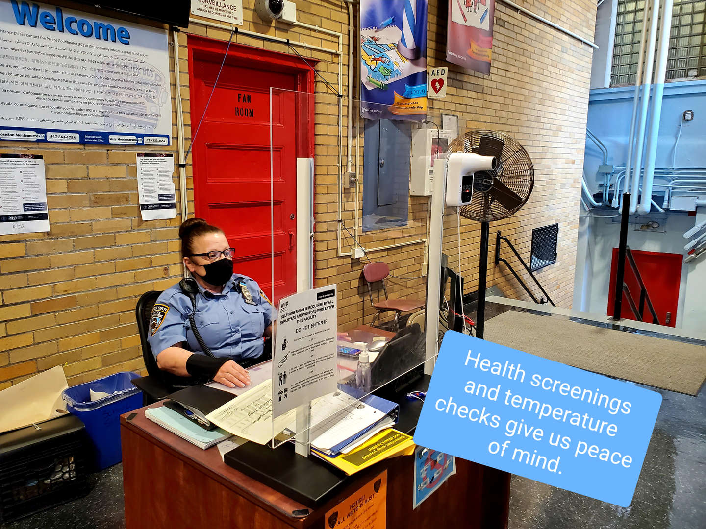 School safety agent at desk with plexiglass barrier and wall thermometer.