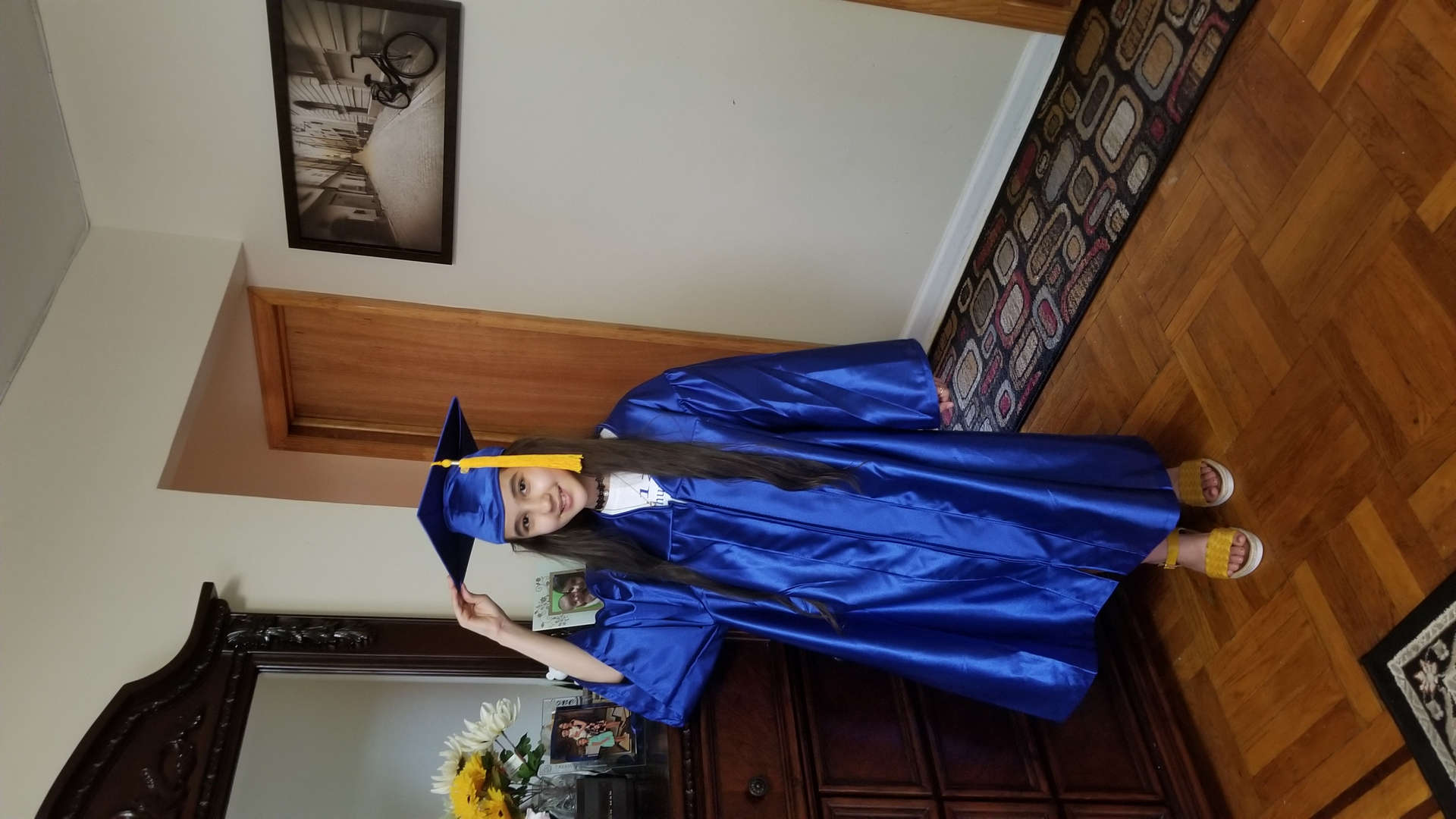 Fifth grade graduate at home with cap and gown