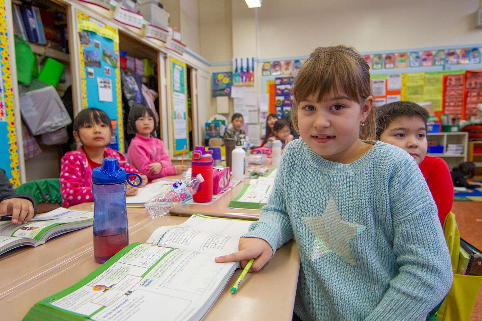 Girl pointing to worksheet on her desk