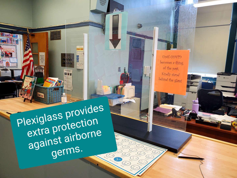 Plexiglass barrier on counter in main office.