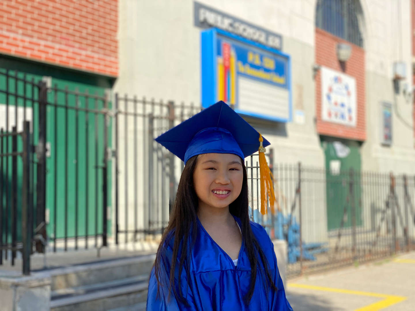 Fifth grade graduate smiling in front of school with cap and gown