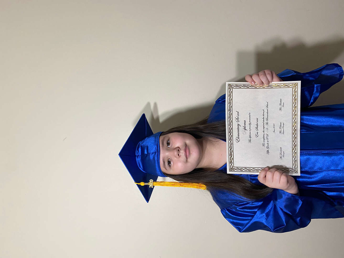 Fifth graduate holding her diploma