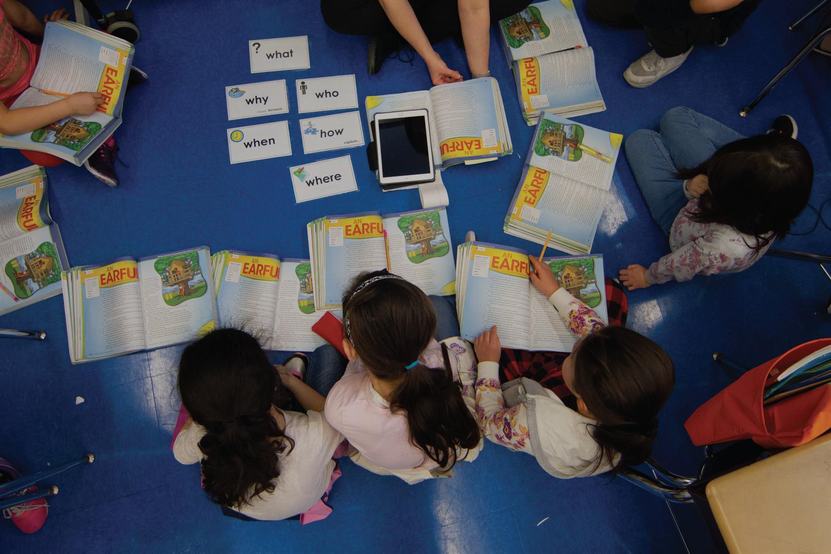Students gathered around books on floor