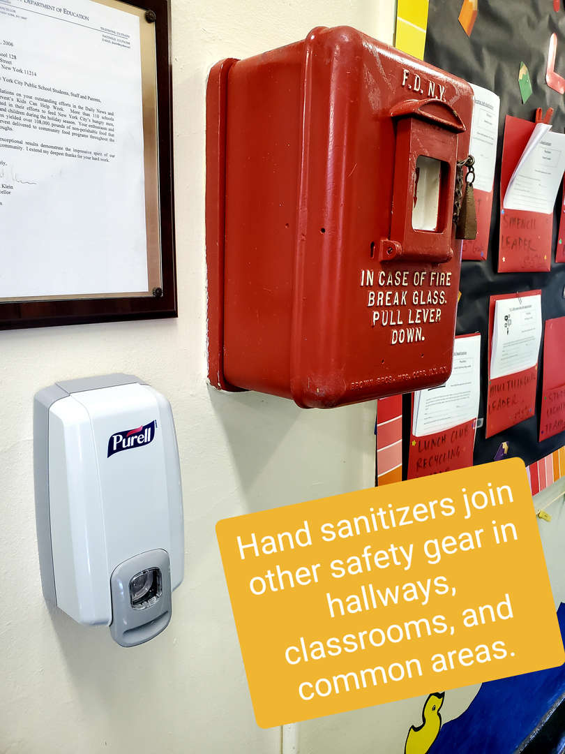 Hand sanitizer on wall next to fire bell.