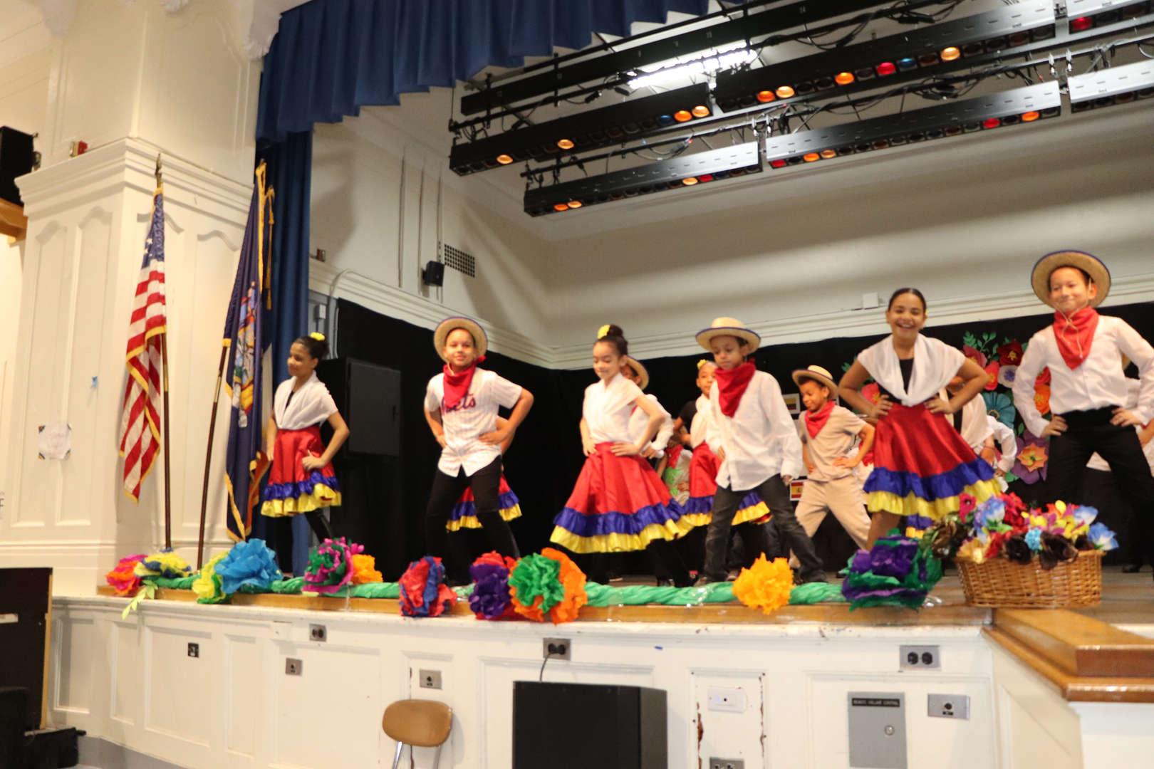 Students on stage dancing in colorful costumes