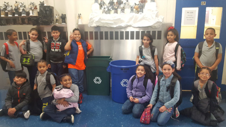 Students in The Green Team posing with their recycling bins