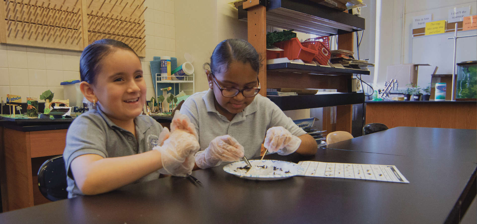 Two students working in the lab with their gloves on
