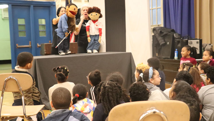 Students gathered watching a puppet show