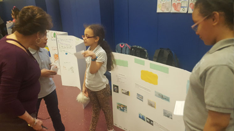 Student presenting their work during a Critical Issues exhibition