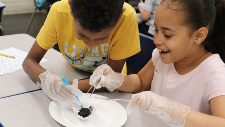 Two students in science class examining an object with tweezers
