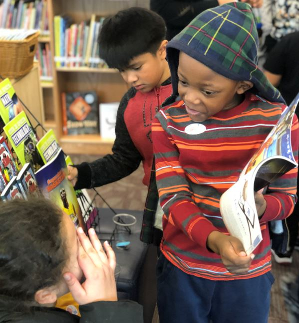 Student shares a book in the library.