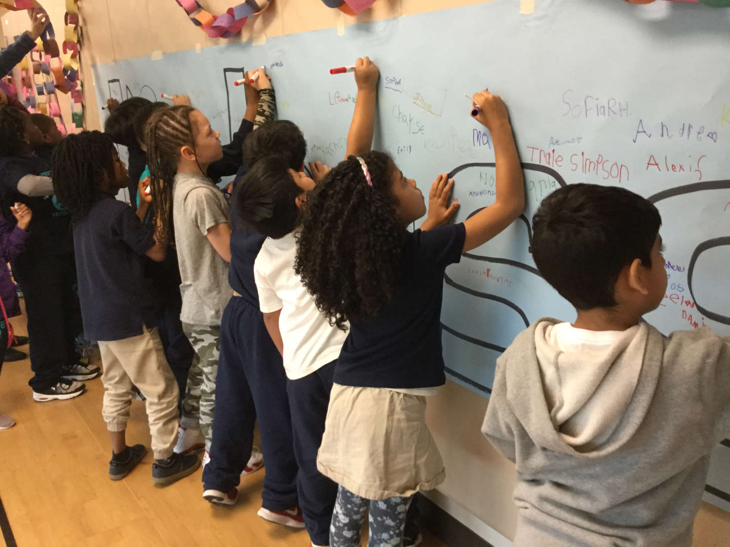 Kids sign their name to the mural.