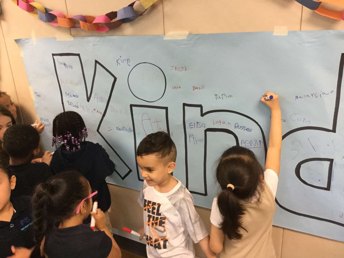 Child writing their name on a kindness poster