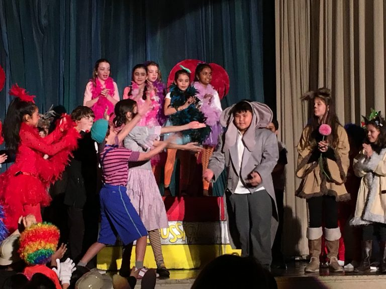 Students on stage dressed in costumes