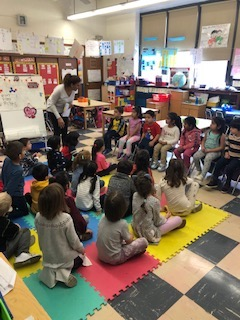 Students gathered in a classroom, listening to the teacher