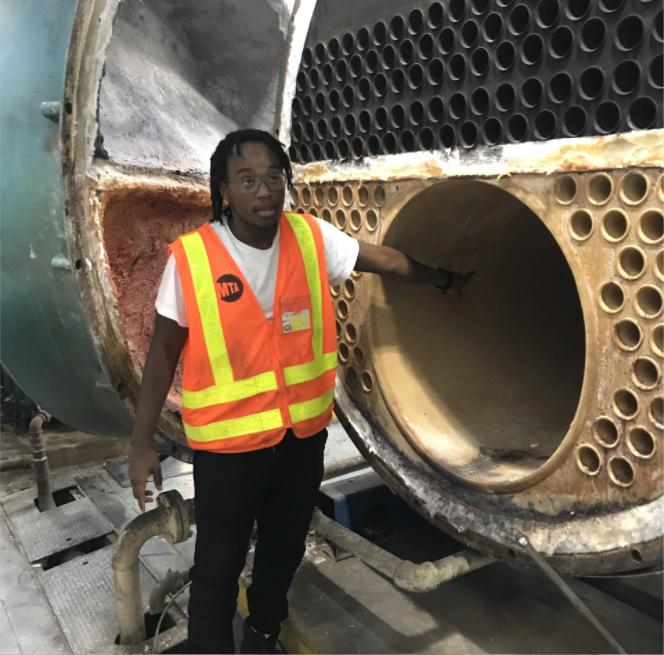 Man wearing MTA vest, pointing inside metal tubing