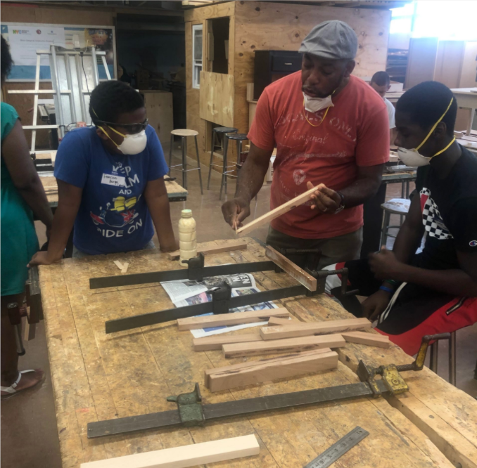 Teacher performing carpentry demo to two students