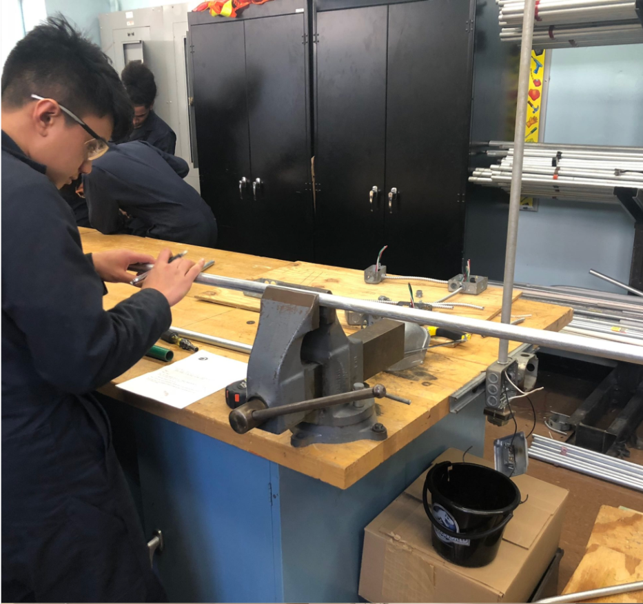 Student marking and adjusting metal tube between clamps