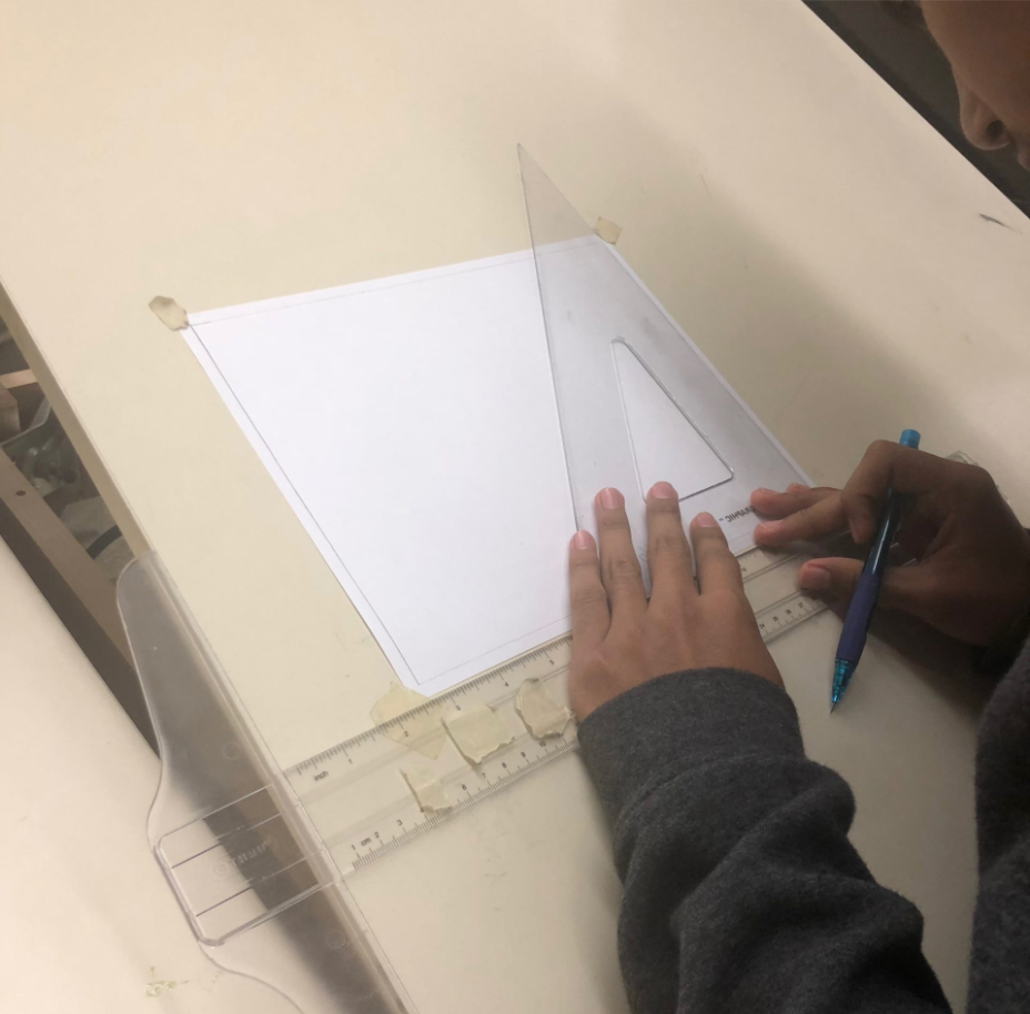 Student preparing their drawing with a ruler and set triangle