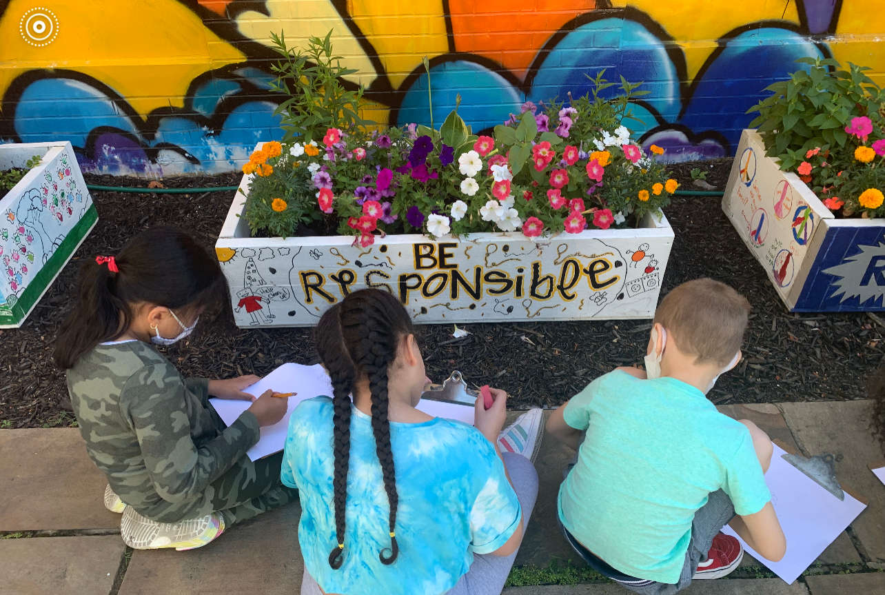 students writing in garden