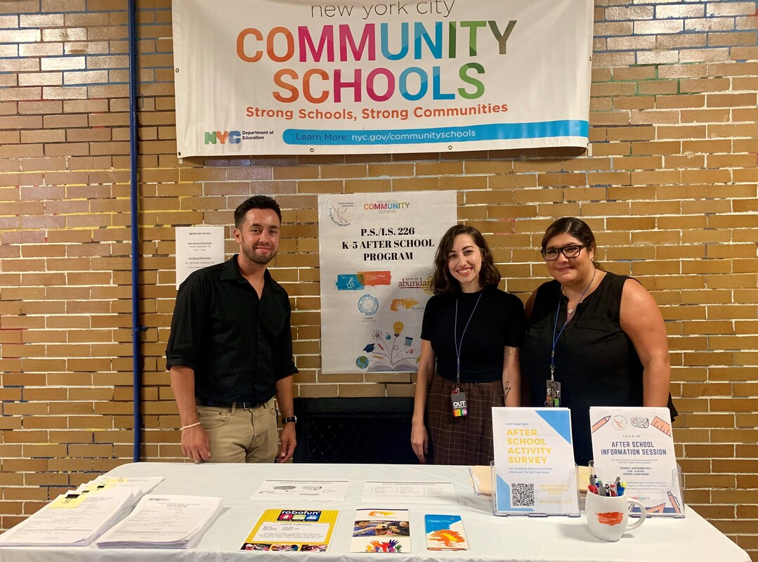 Man and two women standing at after-school information booth