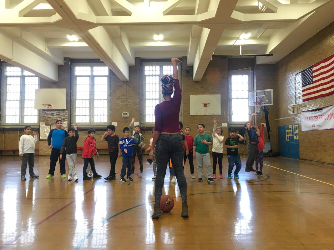 Teacher demonstrating how to shoot a basketball