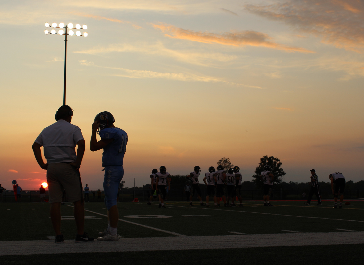 Football player on field with coach.