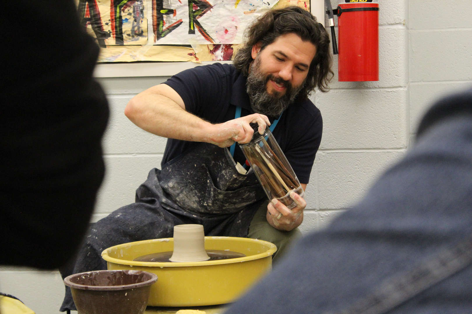 Art teachers shows students how to mold clay.