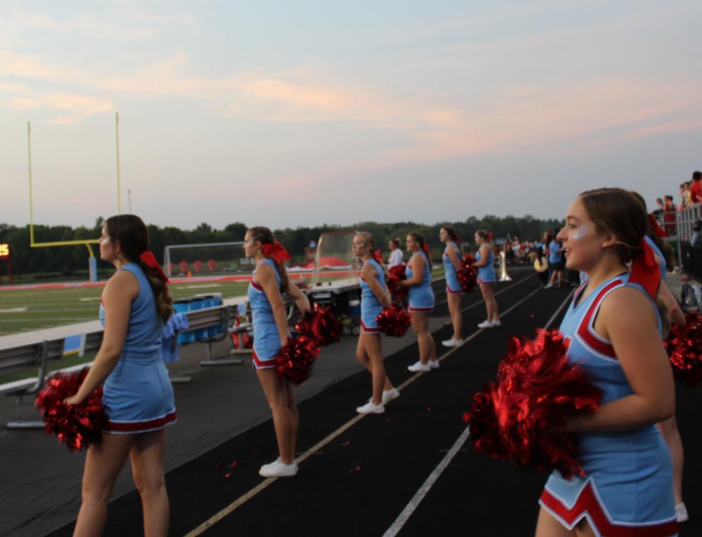 Cheerleaders cheering during football game.
