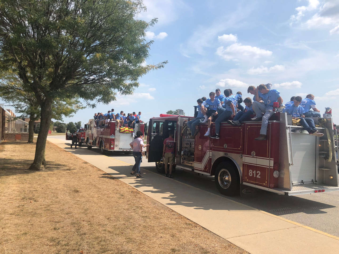 Football team on firetruck during homecoming parade.