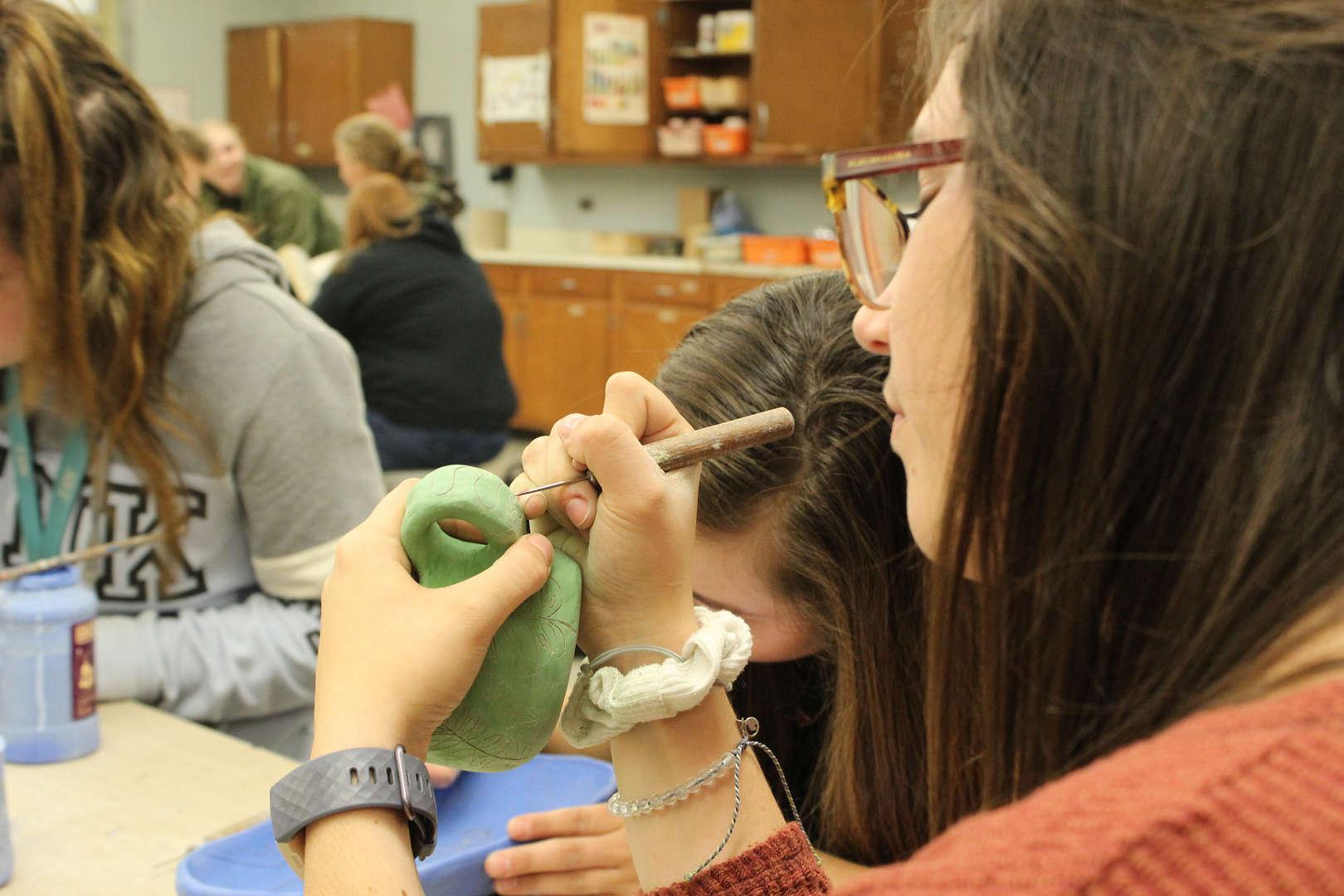 Student carving details into her handmade mug.