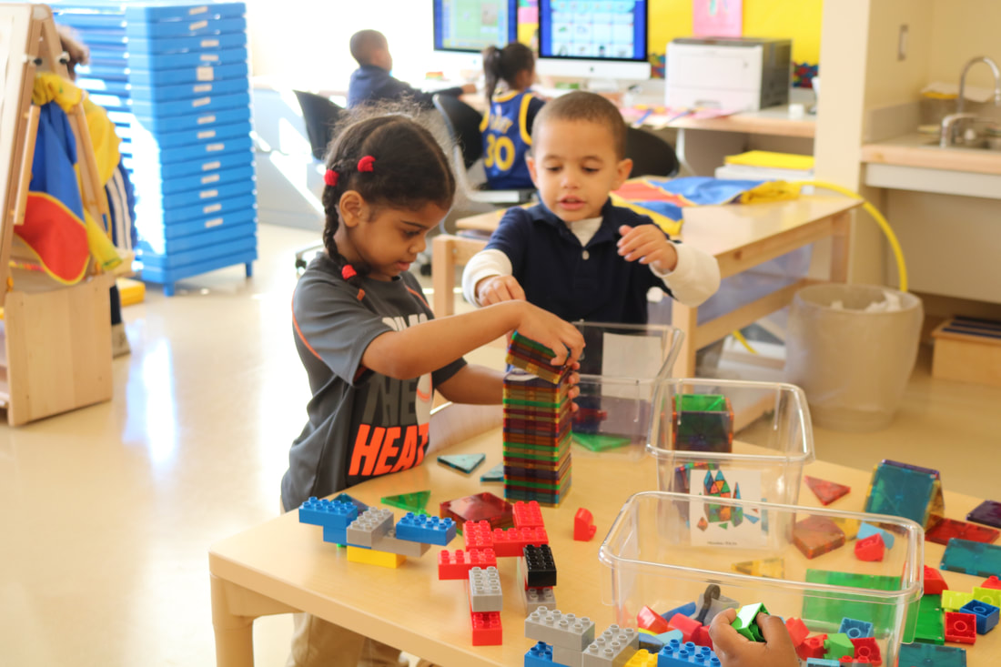 Two students working on building blocks
