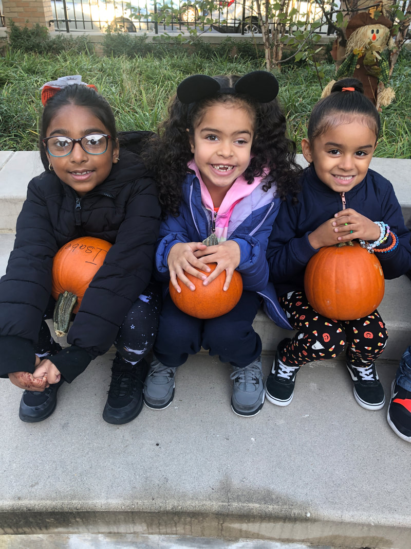 Three students with their pumpkins in their laps