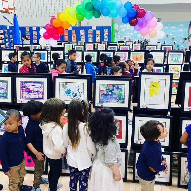 Students looking at art displayed at art show