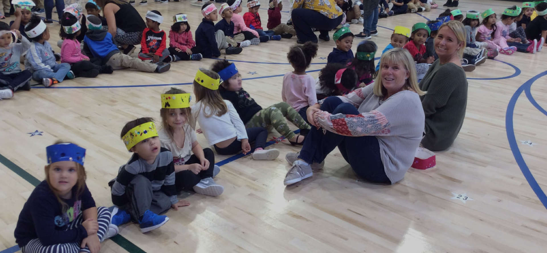 Students and teacher sitting on the gymnasium floor